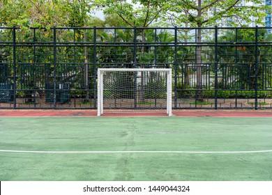 Soccer goal with net in green rubber field
