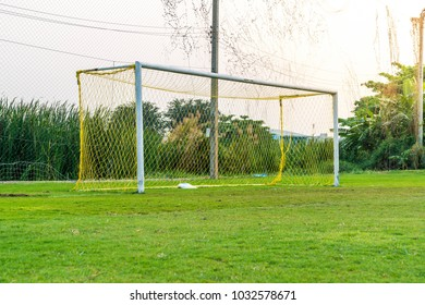 A soccer goal on green empty football field