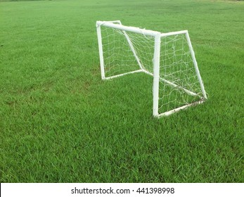 Soccer goal on the green grass field at upcountry in Thailand