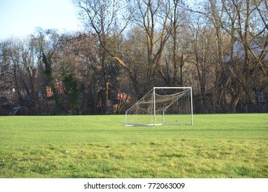 Soccer goal on a green lawn in a sunny day