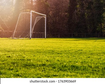 Soccer goal post in a green field, Selective focus, Warm sunny day, Sun flare, dark trees in the background. Concept football training.