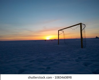 Soccer goal post on Nallikari Beach, Oulu, Finland. Sunset view of a snow-covered playing field.