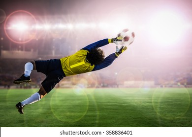 soccer goalkeeper catches the ball on stadium light background