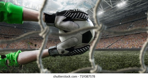 Soccer goalkeeper catches a ball. View through the football goal. Behind him a big professional arena. Goalkeeper wears unbranded clothes.