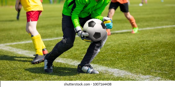 Soccer Goalkeeper Holding Soccer Ball. Soccer Goalkeeper Catching Skills. Youth Football Teams Compeeting in School Soccer Tournament