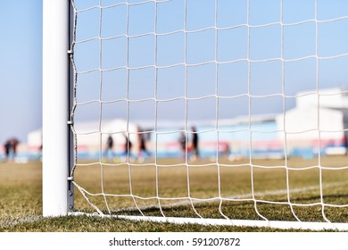 Soccer goalpost and players training in the background