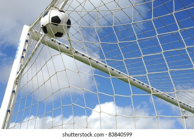 soccer gool, the ball into the net against blue sky
