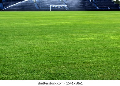 A soccer grass field is watered in the evening.