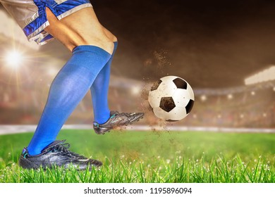 Soccer player in action with football in brightly lit outdoor stadium. Focus on foreground and soccer ball with shallow depth of field on background and copy space.