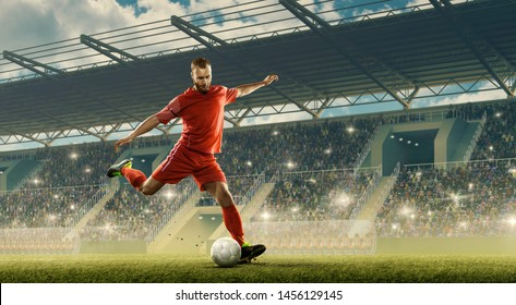 Soccer player with a ball in action. Stadium with tribunes and cheering fans