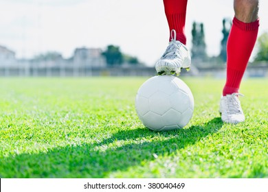 Soccer player with ball on a playing field