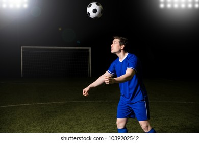 Soccer player in blue uniform heading a football on sports field