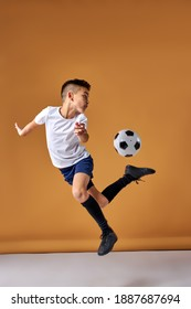 soccer player boy is jumping with ball, practice and training before match, in studio