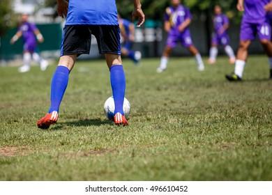 soccer player doing kick with ball on football stadium field