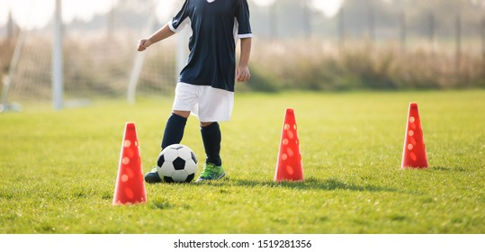 Soccer player dribbling through cones in the ground on a sunny. Young boy soccer (european football) player dribble through cones