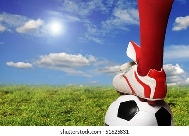 soccer player foot and ball in the pitch