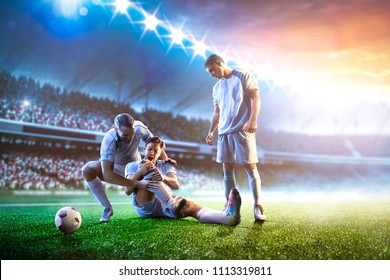 Soccer player helps onother one on sunset stadium background panorama