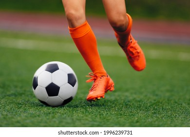 Soccer player hits the ball on the artificial turf. Footballer in sports cleats kicking ball. Legs of footballer playing competition match