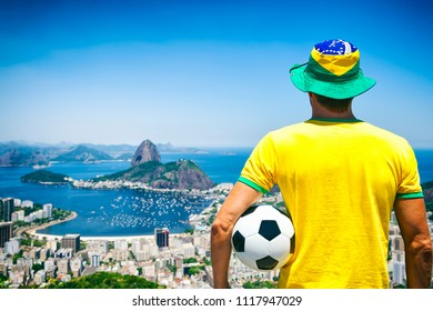 Soccer player holding football wearing shirt and hat in Brazil colors at Rio de Janeiro skyline with Sugarloaf Mountain