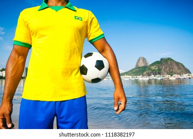 Soccer player holding football wearing shirt in Brazil flag colors at Sugarloaf in Rio de Janeiro