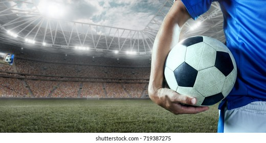 Soccer player holds a soccer ball on a professional stadium. Player wears unbranded clothes.