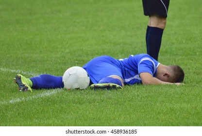 soccer player injured lying on the grass with a ball