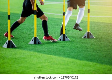soccer player Jogging and jump between marker and yellow hurdles. Soccer training with running slalom around yellow training sticks.