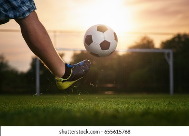 Soccer player kicking a ball in to the goal, sunset in the background