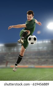 Soccer Player Kicking the ball inside a stadium at night