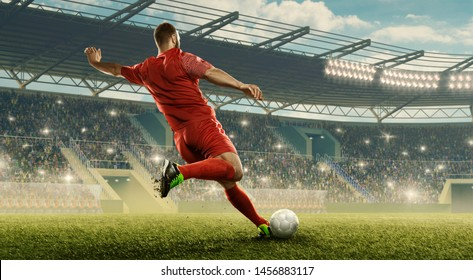 Soccer player kicks of the ball. Action. Floodlit stadium with tribunes.