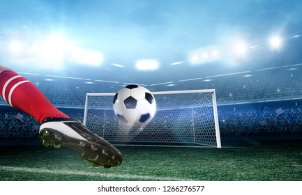 Soccer player kicks the ball on the soccer stadium
