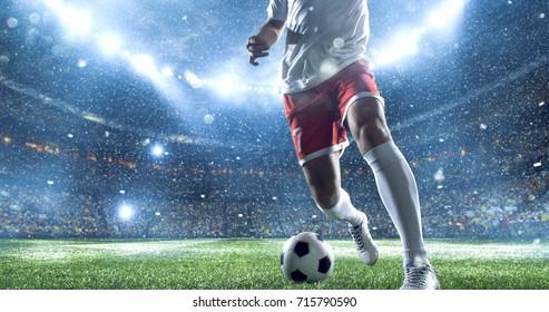 Футболист бьет мяч на футбольном стадионе. Он носит небрендированную спортивную одежду. Стадион и толпа сделаны в 3D.