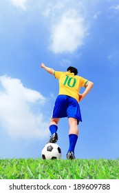 Soccer player man with ball at the stadium with blue sky