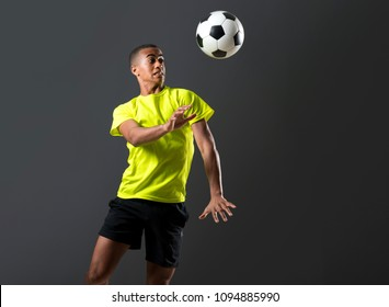 Soccer player man with dark skinned playing hitting head on dark background