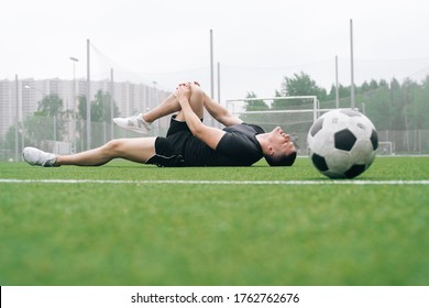 soccer player A man holds his knee. Dislocation of the knee joint. The concept of falling during sports. Break your leg in training