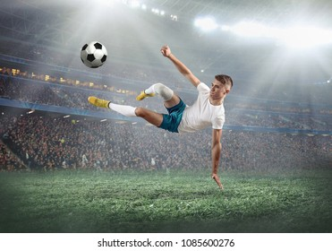 Soccer player on a football field in dynamic action at summer day under light of stadium. Sporty man is shooting the ball outdoor.