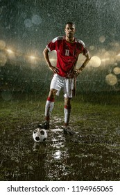 Soccer player on professional soccer night rain stadium. Dirty player in rain drops hold a football ball