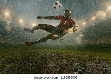 Soccer player on professional soccer night rain stadium. Dirty player in rain drops kicks the football ball in flight