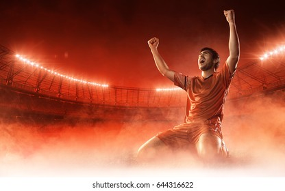 soccer player on soccer stadium celebrating a goal on red smoke background