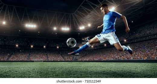 Soccer player performs an action play on a professional stadium. Football players wear unbranded clothes. The stadium is made in 3D.