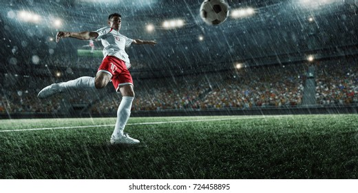 Soccer player performs an action play on a professional rainy stadium. Player wears unbranded clothes. The stadium is made in 3D.
