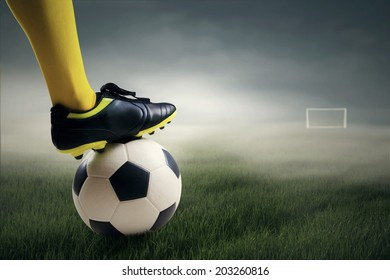 Soccer player ready to kick the ball leads to the gate at field