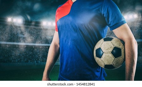 Soccer player ready to play with ball in his hands at the stadium