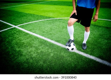 Soccer player ready to play at kick off point in soccer field.