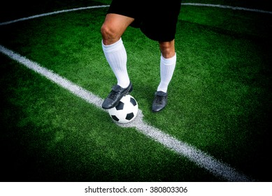 Soccer player ready to play at start kick off point in soccer field.