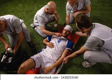 Soccer player received a head injury during the game. Sport Doctors provide first aid to player on a professional football field