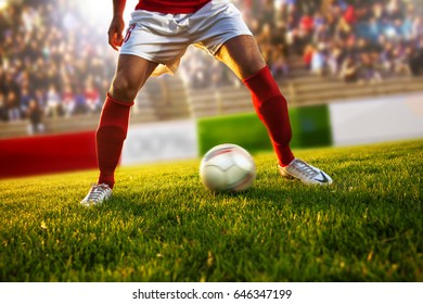 Soccer player with red socks in dribble position.Stadium is blurred behind him.