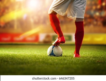 Soccer player with red socks preparing for free kick.Stadium is blurred behind him.
