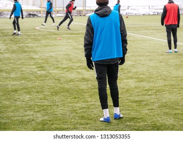 Soccer player running after the ball, legs in action. Football training session. Teenagers improving soccer skills in the cold off season.