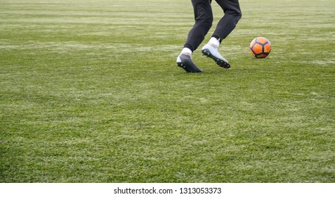 Soccer player running after the ball, legs in action. Football training session. Teenagers improving soccer skills in the cold off season. Copy space.